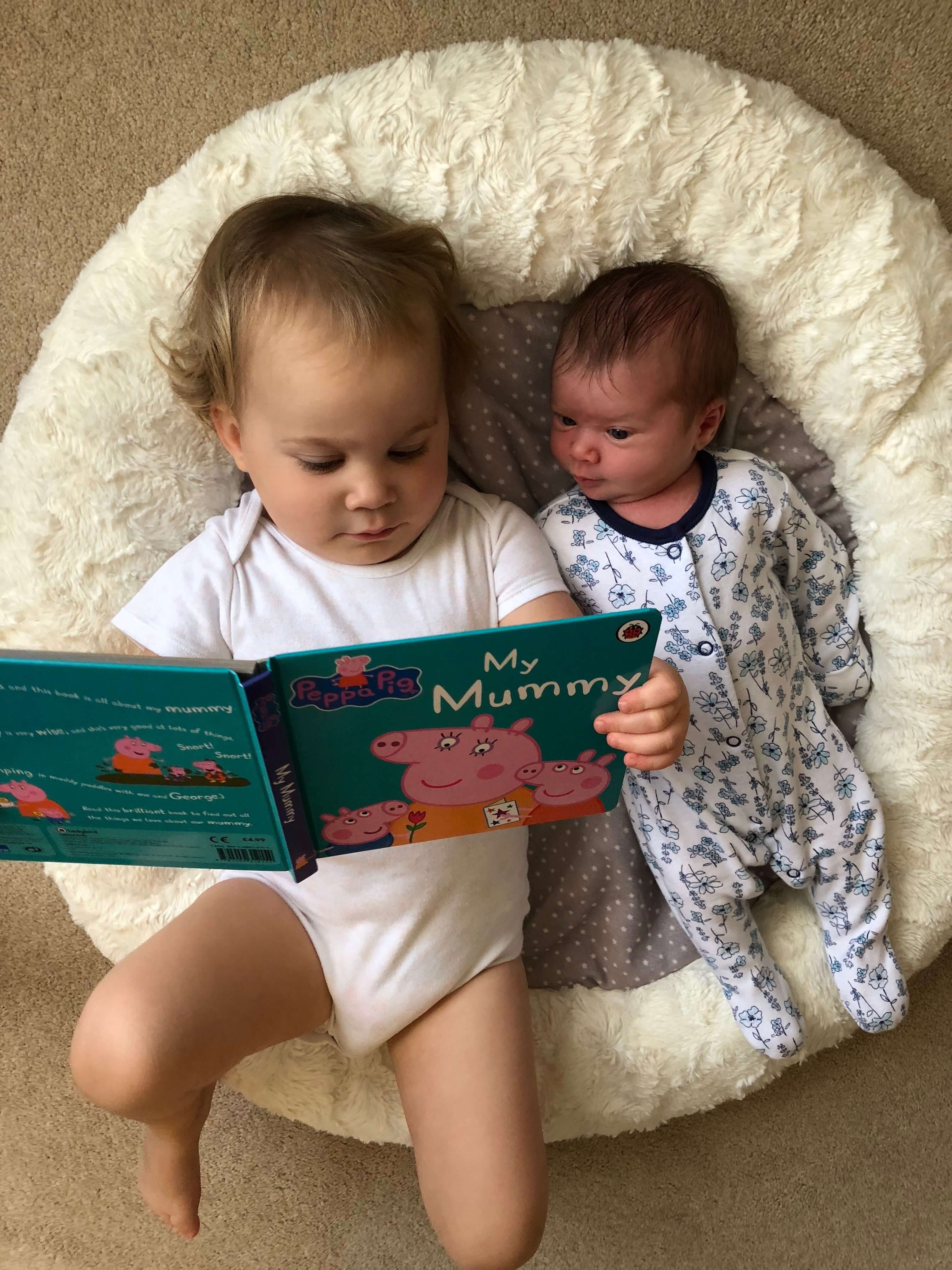 A toddler reads a book to her baby sister