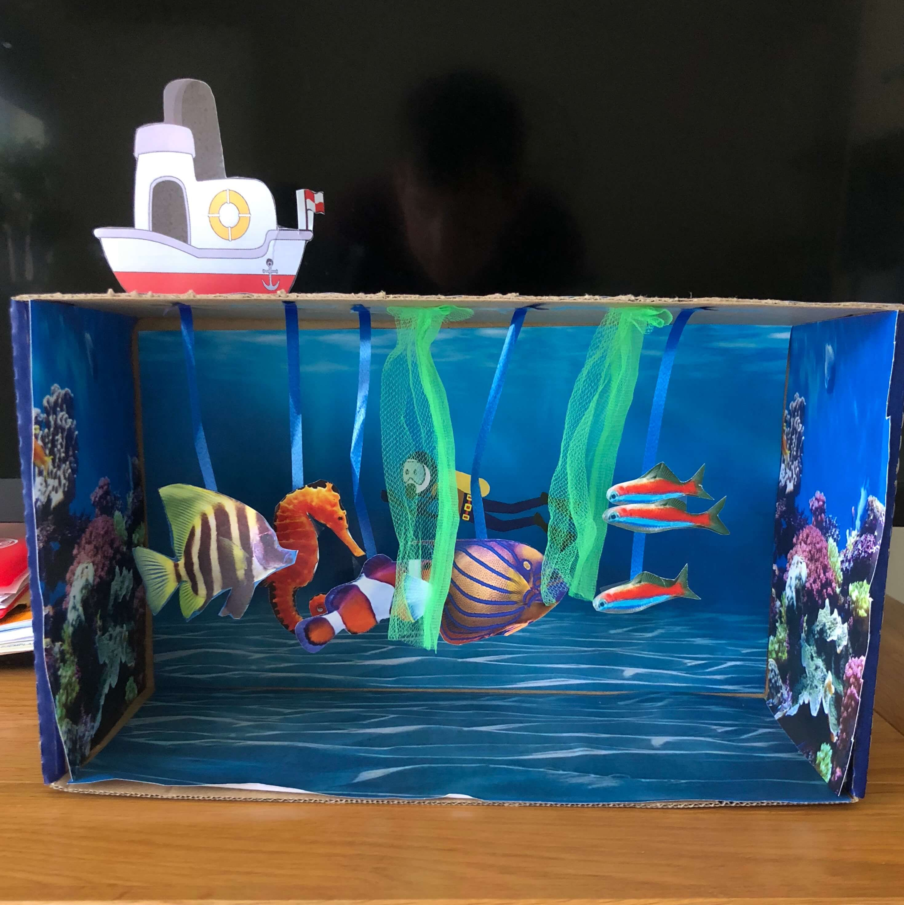 an aquarium which is just bits of paper and ribbon stuck in a shoebox
