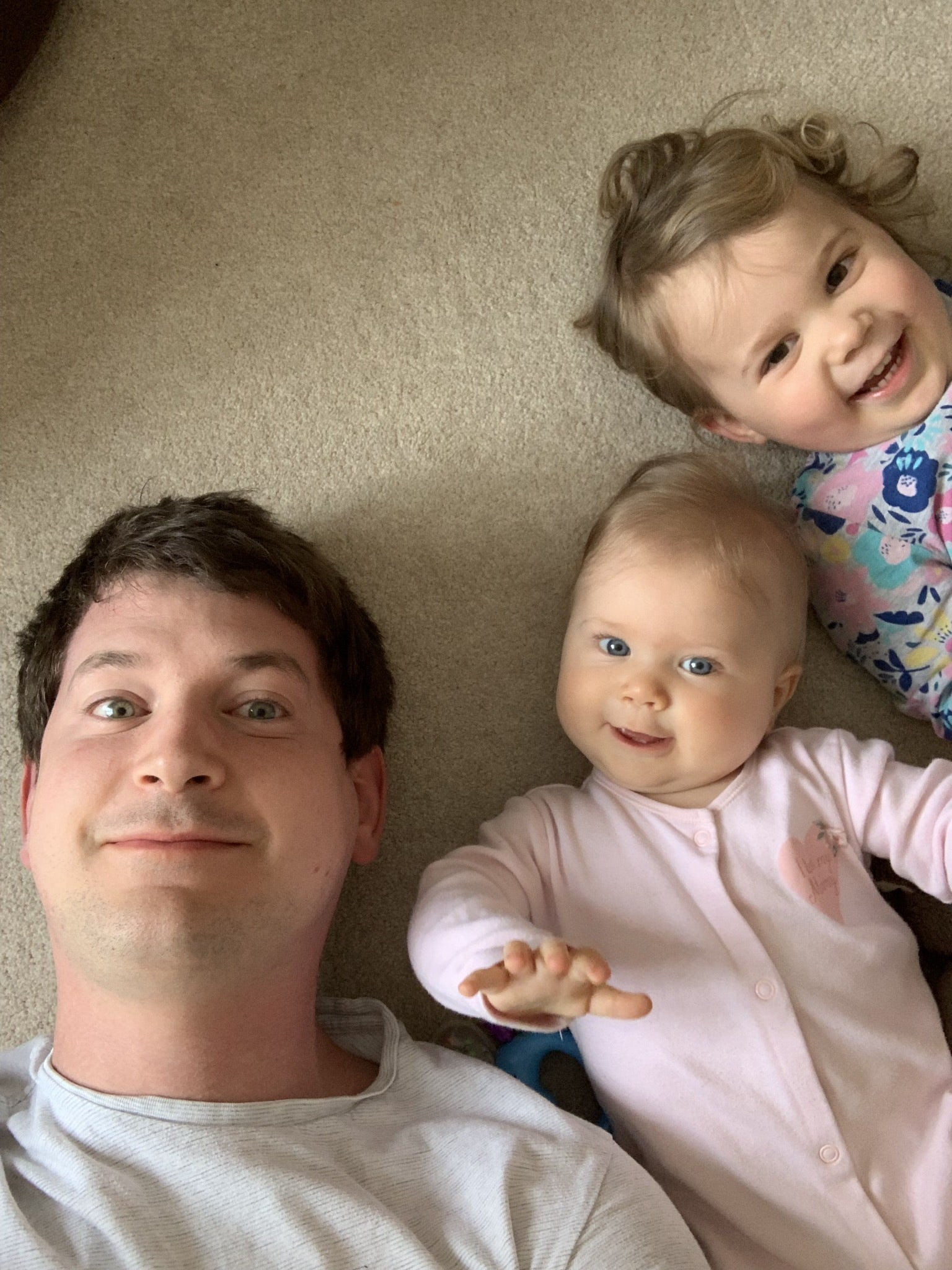 Me and my two kids, lying on the floor, looking up at the camera.