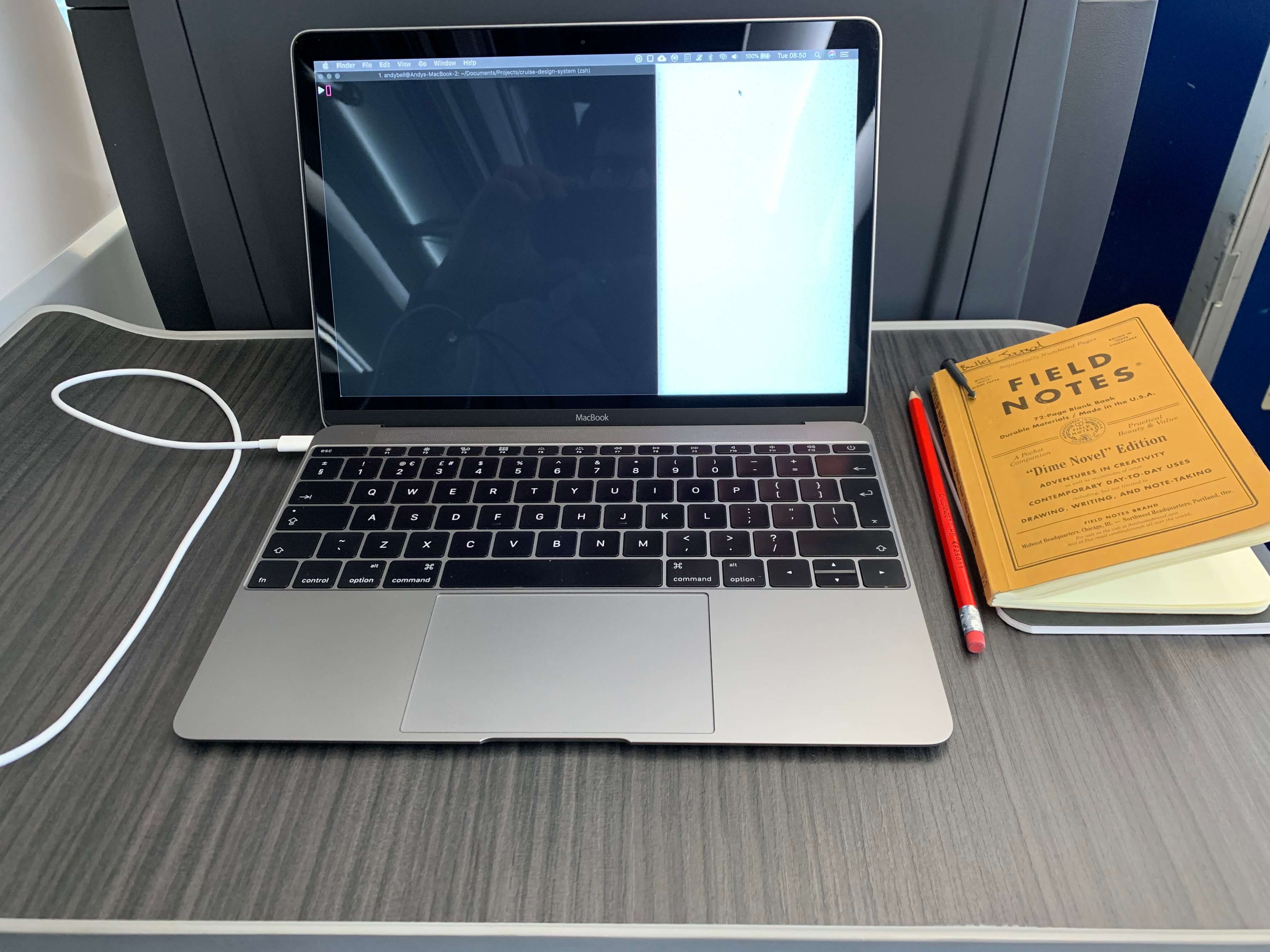 A laptop on a train table with a notebook and pencil