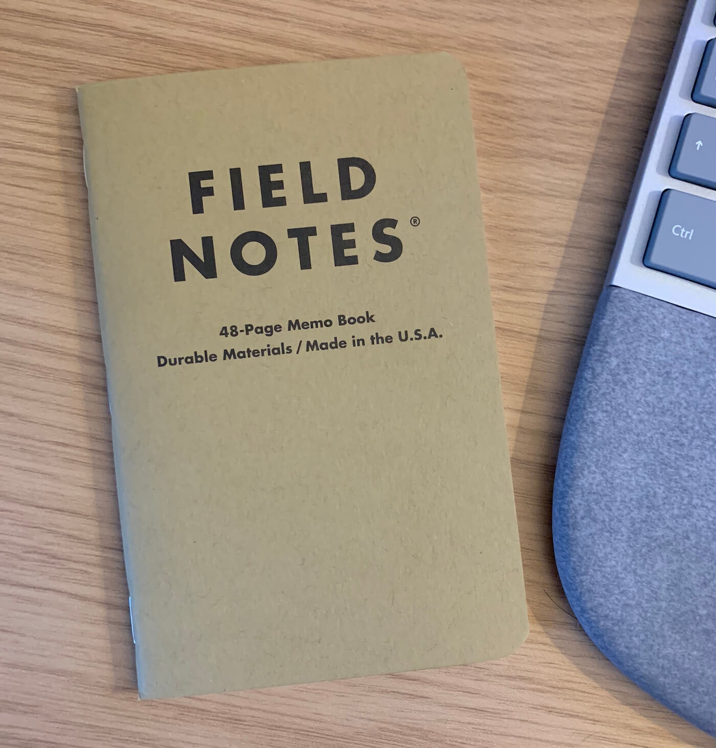 A fresh Field Notes notepad sits on a brown desk, next to a keyboard