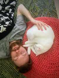 Stephen and a white cat take a nap together