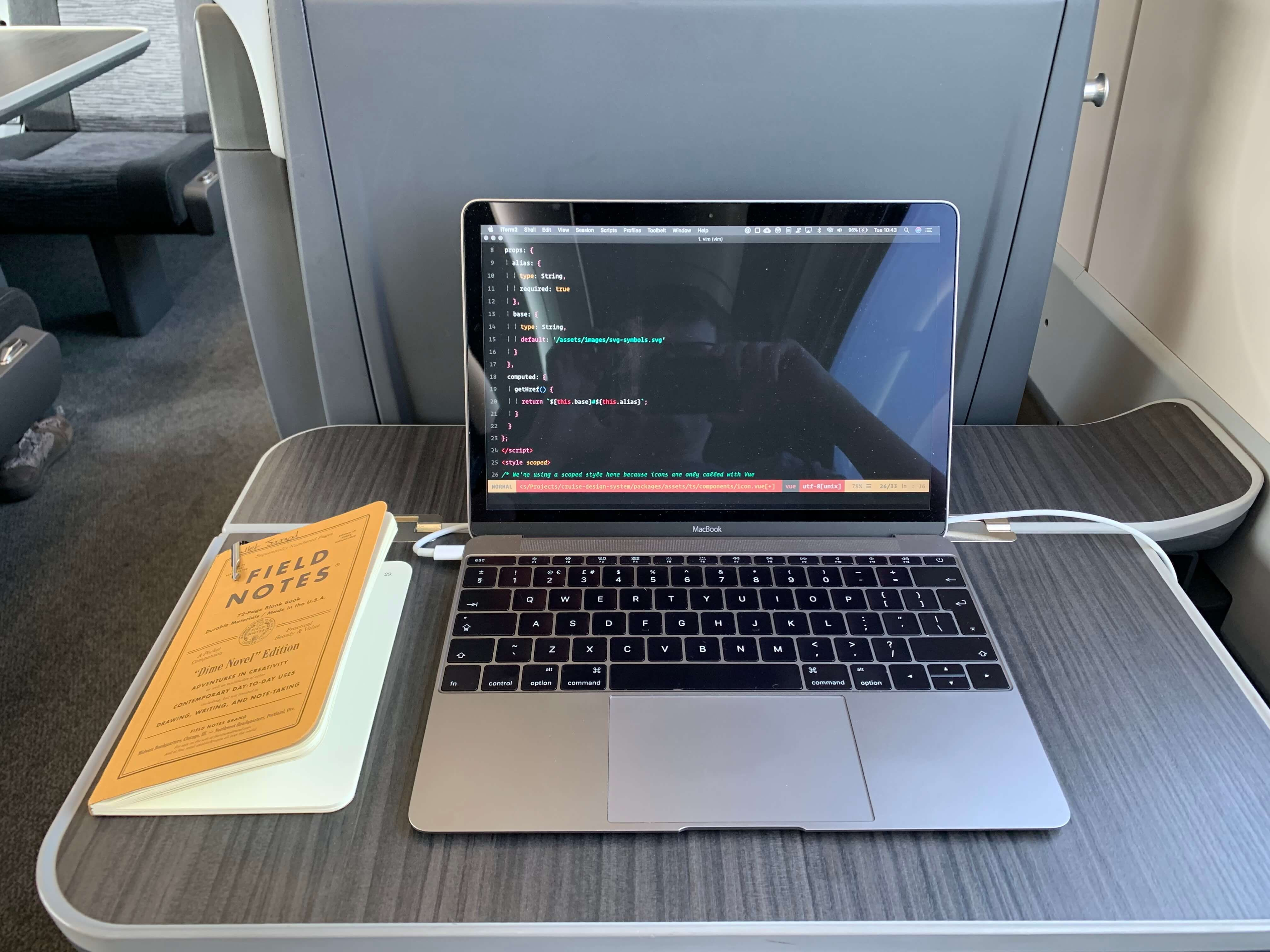 A macbook and field notes notepad on a train desk